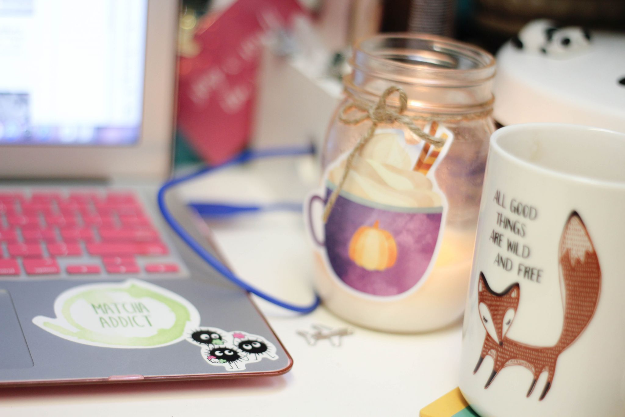 Desk with laptop with tea and anime stickers and a tea mug. Pastels.